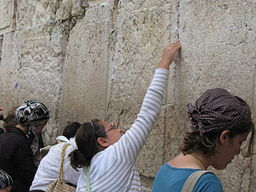 Jewish woman placing a kvitel in the Western Wall. Photo by Yonina via Wikimedia Commons.